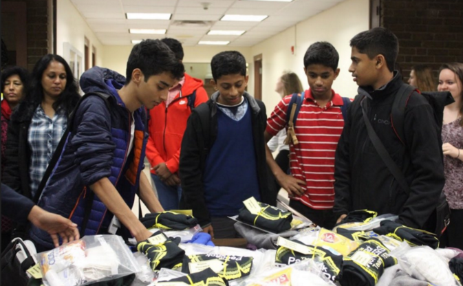 A group of Indian foreign exchange students first arriving at Hills, receiving t-shirts from the robotics team. Photo Source - FRC Team 1676 on Twitter
