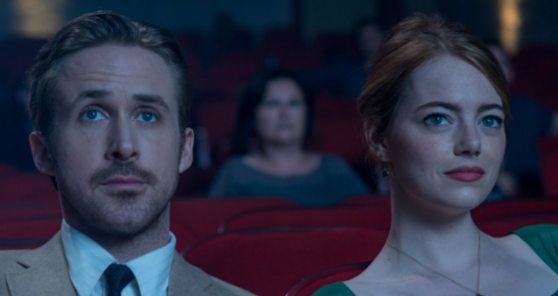 Ryan Gosling/Sebastian (left) and Emma Stone/Mia sitting in a movie theater. Photo by Dale Robinette.