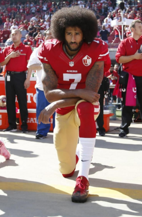 Colin Kaepernick, NFL Quarterback, kneeling during the National Anthem on a televised Sunday football game.