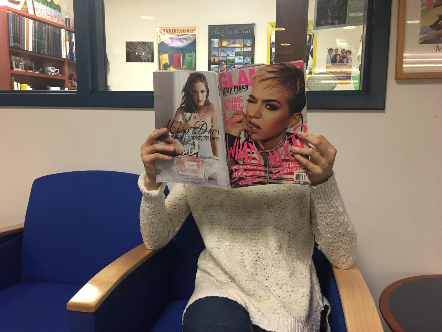 Senior Erin B. reads a magazine about celebrities in the Media Center
