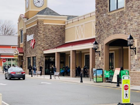 "Customers lined up outside Wegmans on Friday morning. Many wore masks and gloves. A sign on the right reads ""Entrance only"" as the store is controlling the number of shoppers who enter."