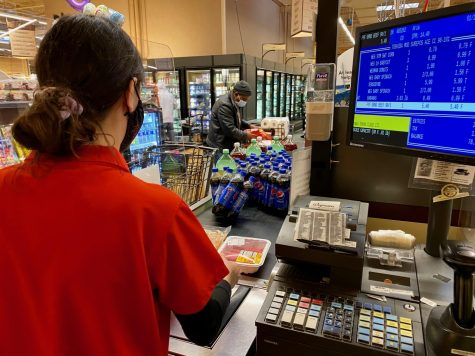 Aria Chalileh, pictured here checking out a customer, is a Hills senior who works part-time as a cashier at Wegmans.