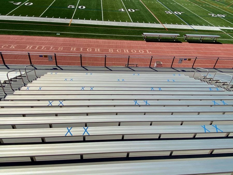 Blue tape marks where spectators can sit socially distant at sporting events.