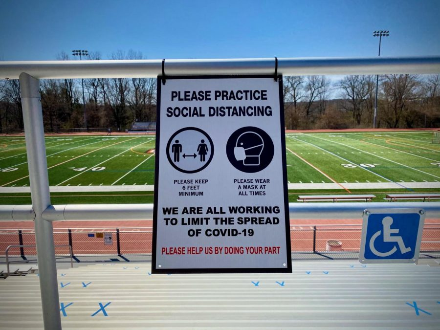 Signage on the bleachers at Hills reminding spectators to wear masks and social distance.
